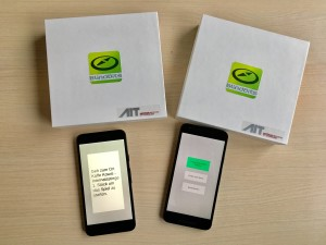 Two smartphones running the BlindBits Game and boxes covered with AIT and BlindBits stickers.