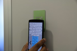 Smartphone with the Blind Bits application touching an NFC card mounted on the wall